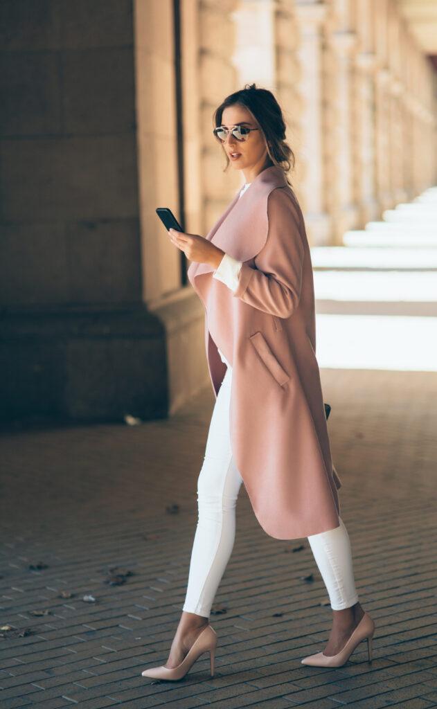kobieta w pudrowych_różowych szpilkach pisze na telefonie.