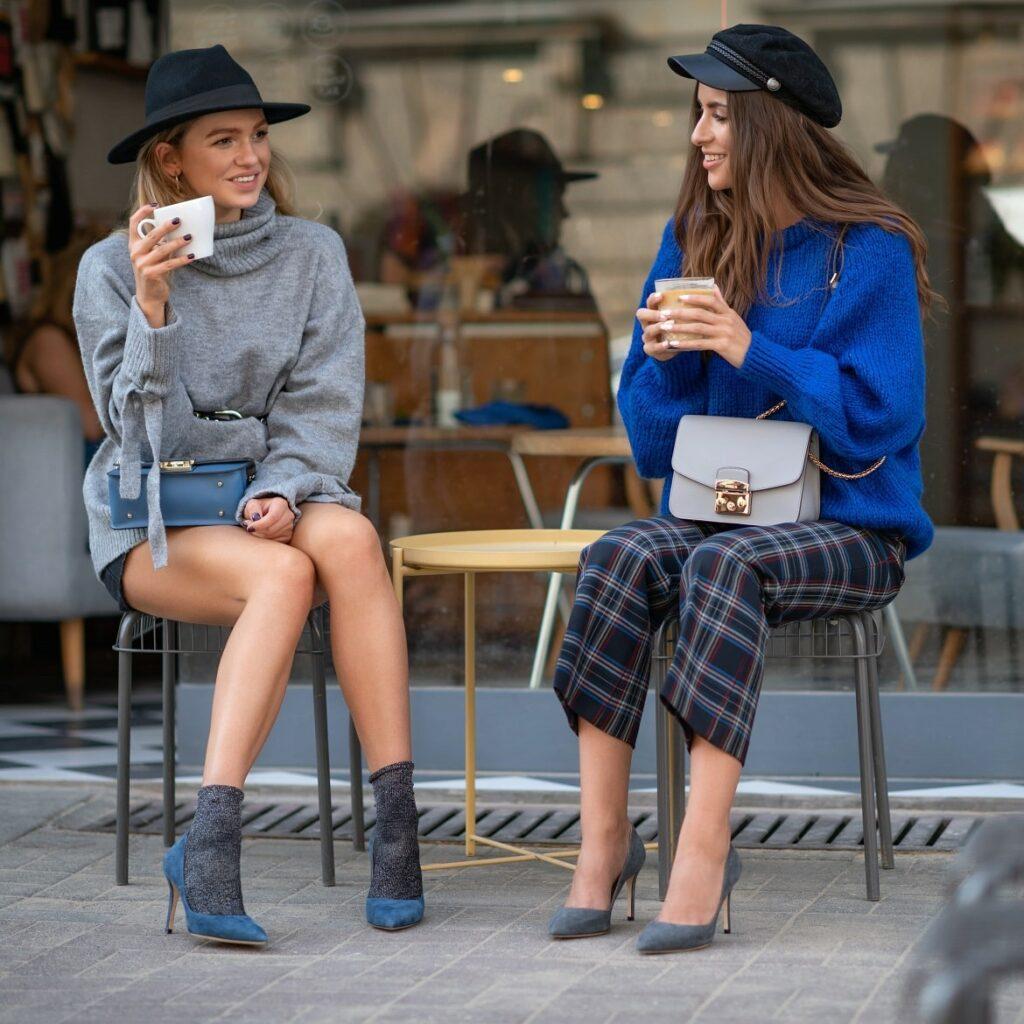 Stylowe kobiety w szpilkach piją kawę
