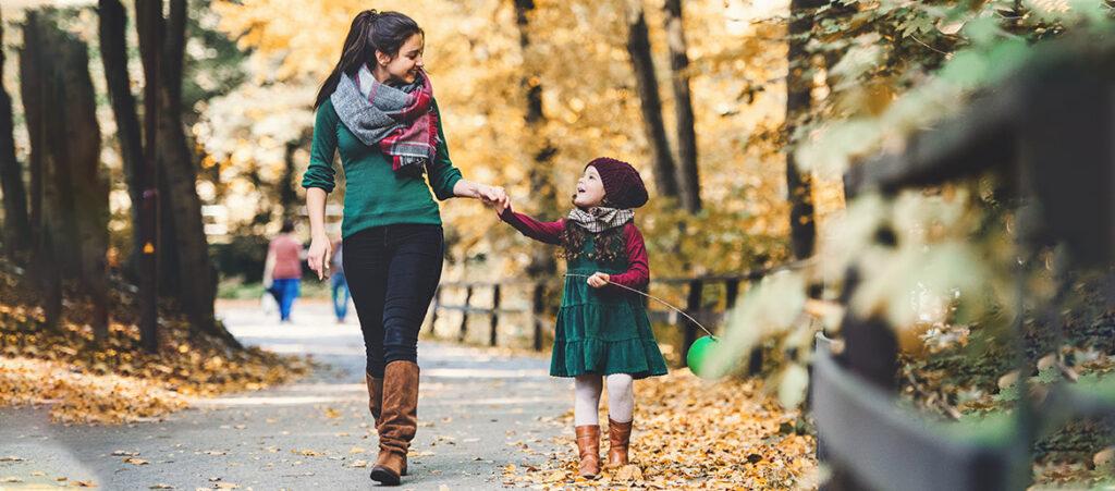 Mama i córka spacerują w parku w kozakach