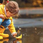Dziewczynka w żółtych kaloszach bawi się na dworze