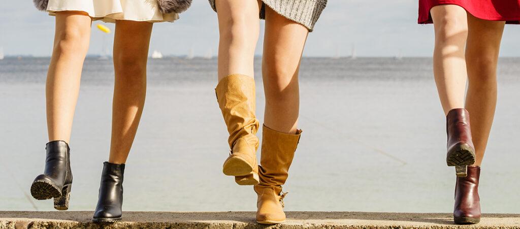 Nogi trzech kobiet w kozakach i botkach