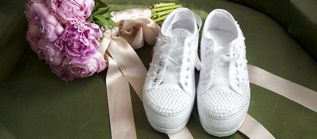 Białe sneakersy damskie do ślubu obok bukietu kwiatów