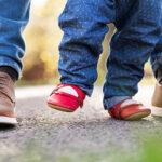 Tata pomagający córeczce stawiać pierwsze kroki