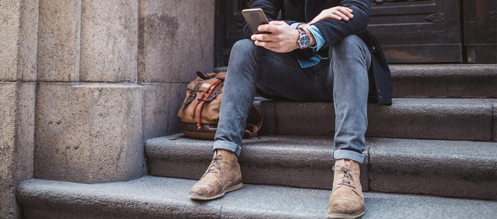 Nogi mężczyzny siedzącego na schodach w jesiennych trzewikach
