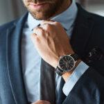 Mężczyzna w garniturze z zegarkiem na ręce poprawia krawat