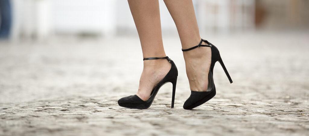 czarne szpilki z paskiem wokół kostki na stopach modelki