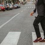 Mężczyzna w mokasynach do garnituru na przejściu dla pieszych
