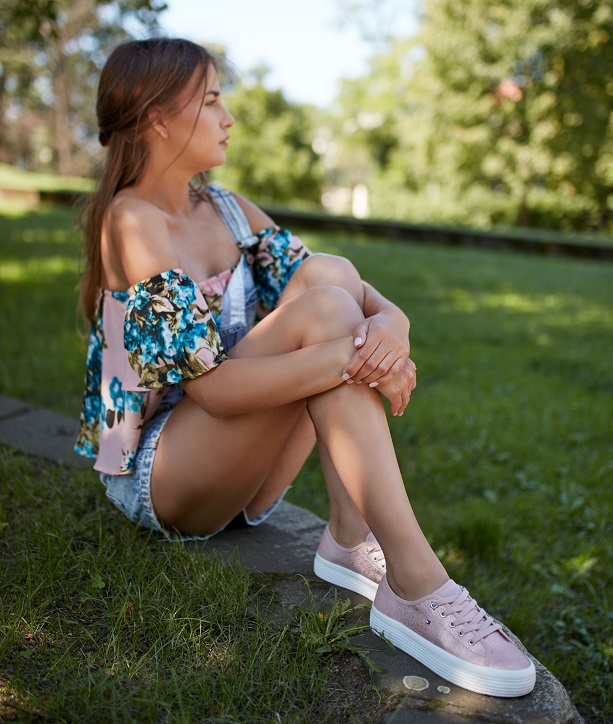 beżowe sneakersy na modelce stylizacja z szortami i bluzką