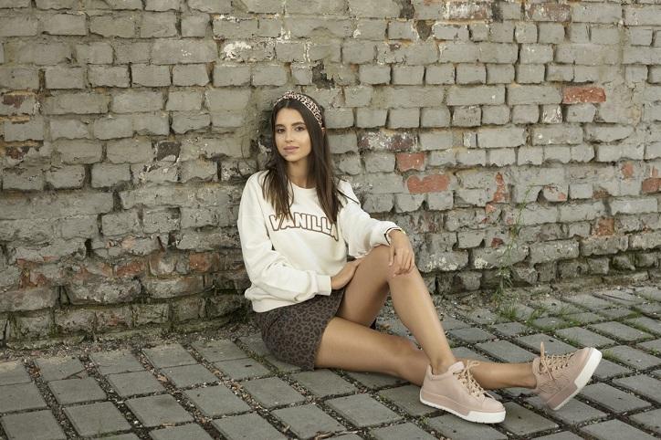 beżowe sneakersy na modelce stylizacja ze spódniczką i bluzą