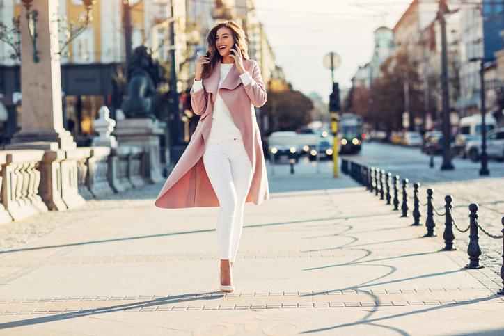 Modelka w białej bluzce, białych jeansach, białych szpilkach i różowym płaszczu