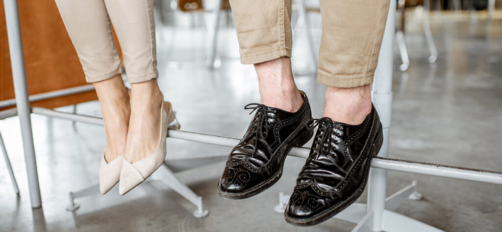 kobieta w białych pantoflach i mężczyzna w czarnych półbutach