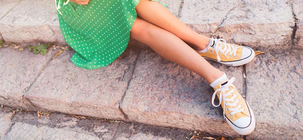modelka w żółtych trampkach i zielonej sukience