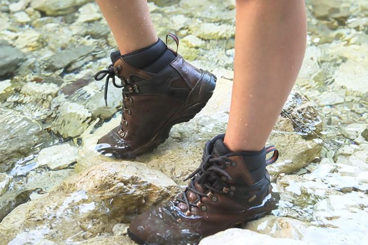 Przekraczanie rzeki w zaimpregnowanych butach trekkingowych