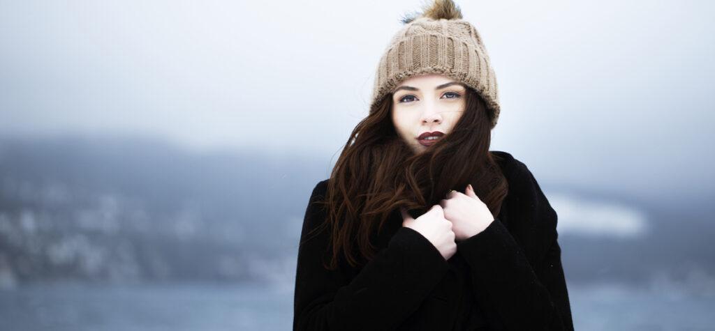 kobieta w płaszczu i czapce z pomponem