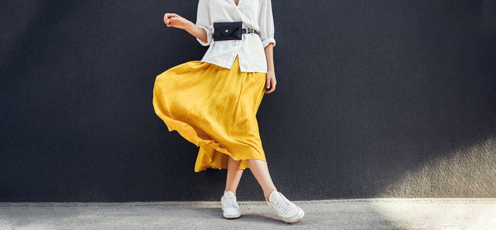 Kobieta w żółtej spódnicy i białych butach