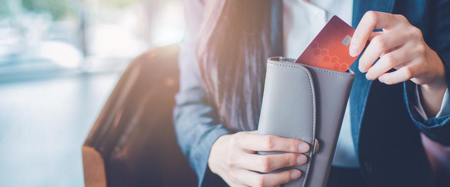 Duży, szary portfel w rękach kobiety