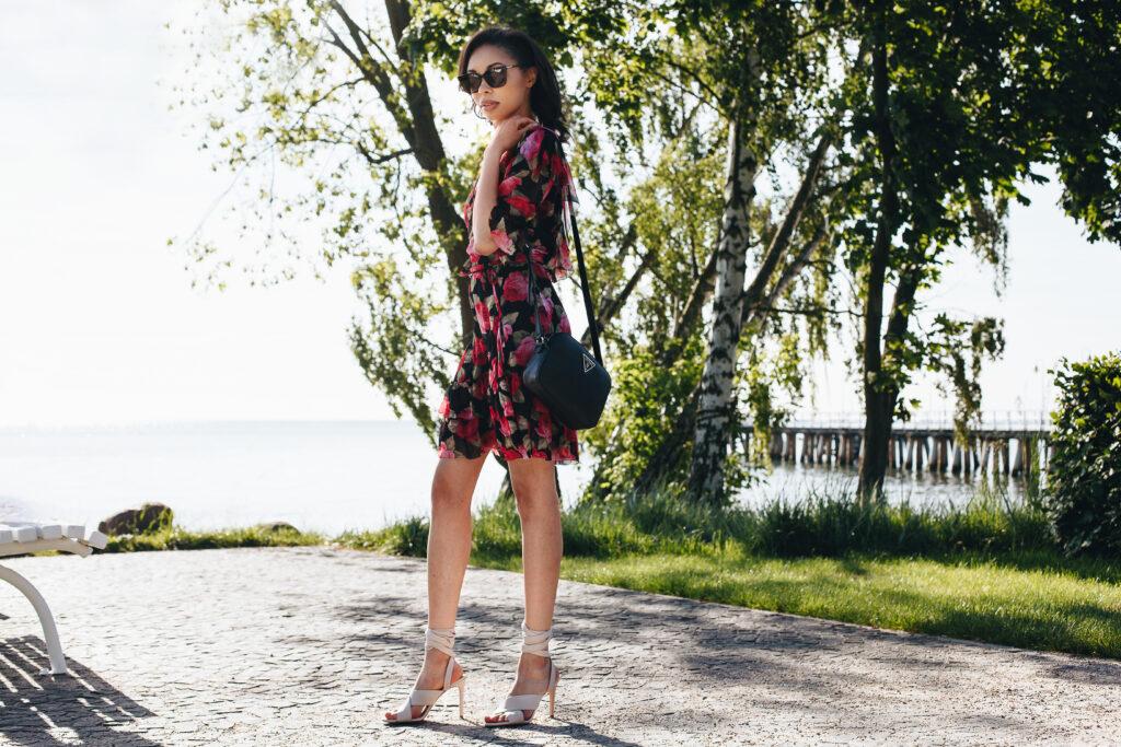 Modelka w białych sandałach i z czarną torebką