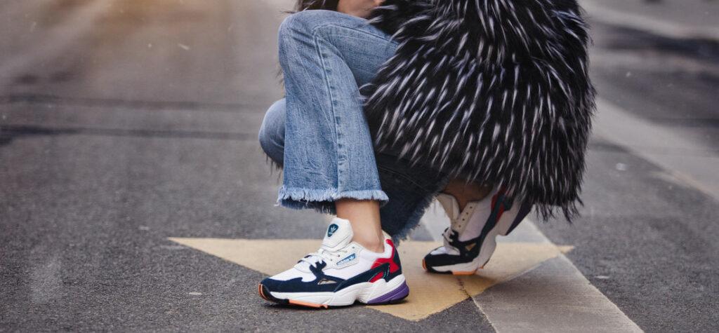 Kolorowe sneakersy z jeansami i płaszczem
