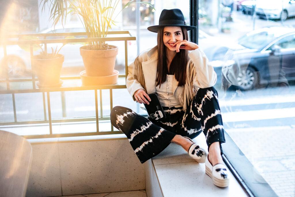 modelka w szerokich spodniach i sneakersach