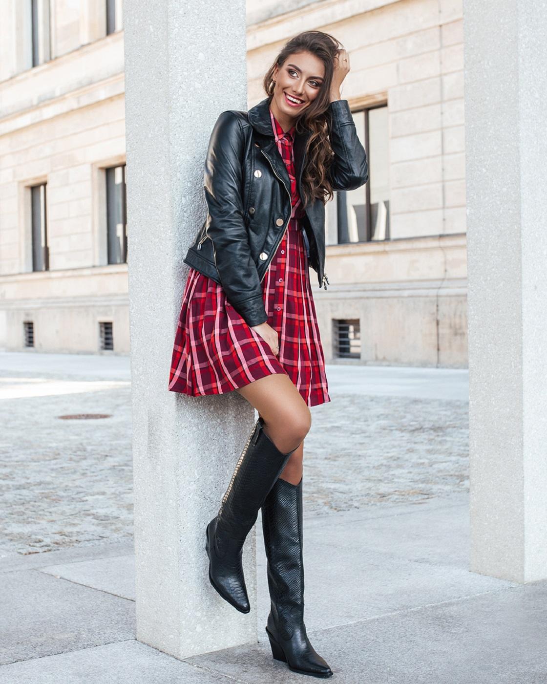 Modelka w stylizacji z kraciastą sukienką i kowbojkami-kozakami.