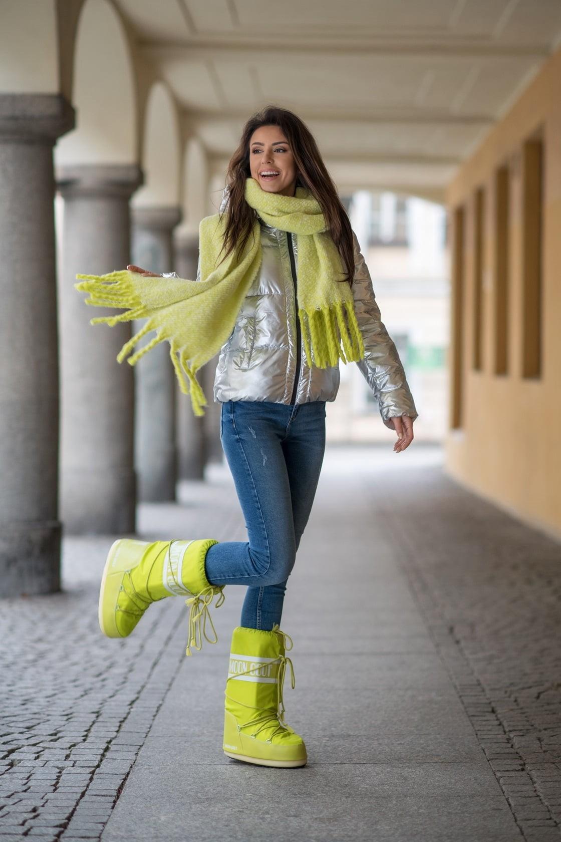 Zimowa stylizacja z moon boots i srebrną kurtką.