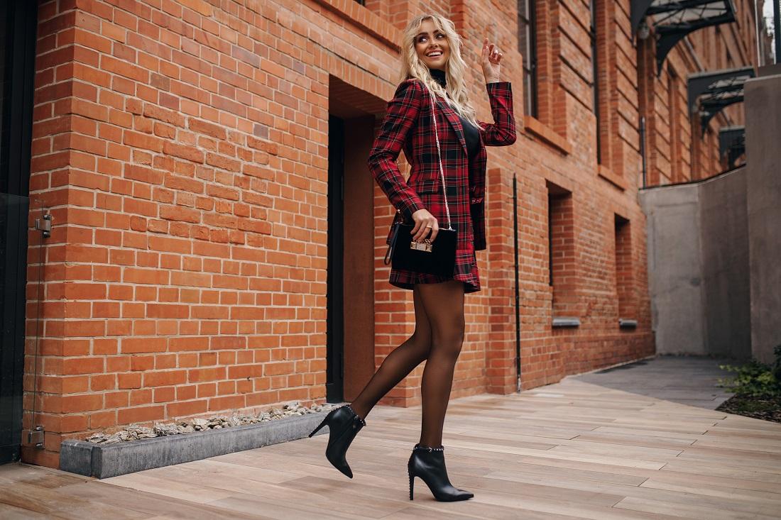 Blondynka w kraciastym żakiecie i czarnych botkach na szpilce