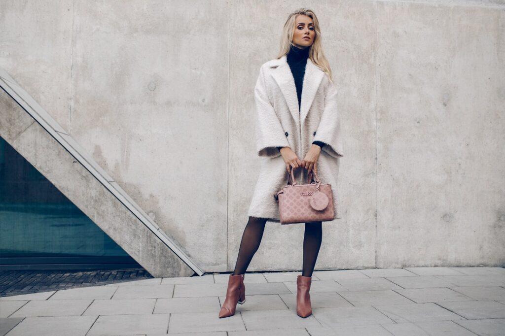 Blondynka w stylizacji z białym płaszczem, camelowymi botkami na słupku i torebką Guess.