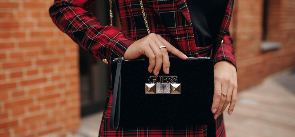 Stylizacja z czarną torebką i płaszczem w kratę