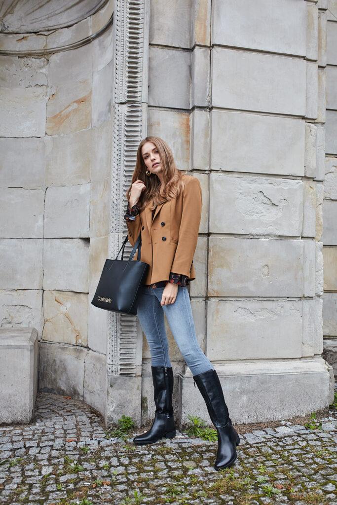 modelka w brązowym płaszczu, jeansach, czarnych oficerkach i z czarną torbą shopper