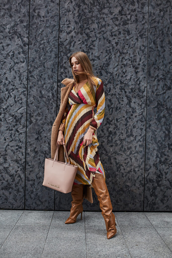 modelka w kolorowej sukience maxi, w kozakach na obcasie i różową torbą shopper