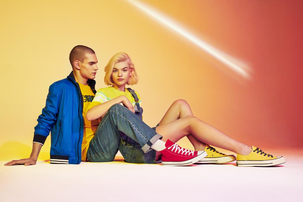 Para młodych ludzi w streetwearowych stylizacjach z trampkami Converse