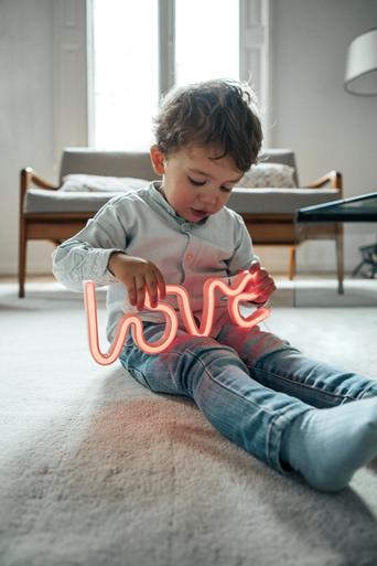 Mały chłopiec bawiący się neonowym napisem love