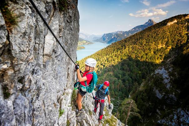 Dziewczynka wspinająca się po skale z tatą