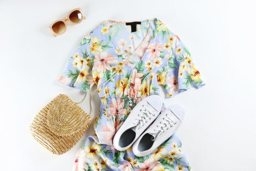 białe trampki, słomiana torebka, kwiecista sukienka, okulary przeciwsłoneczne