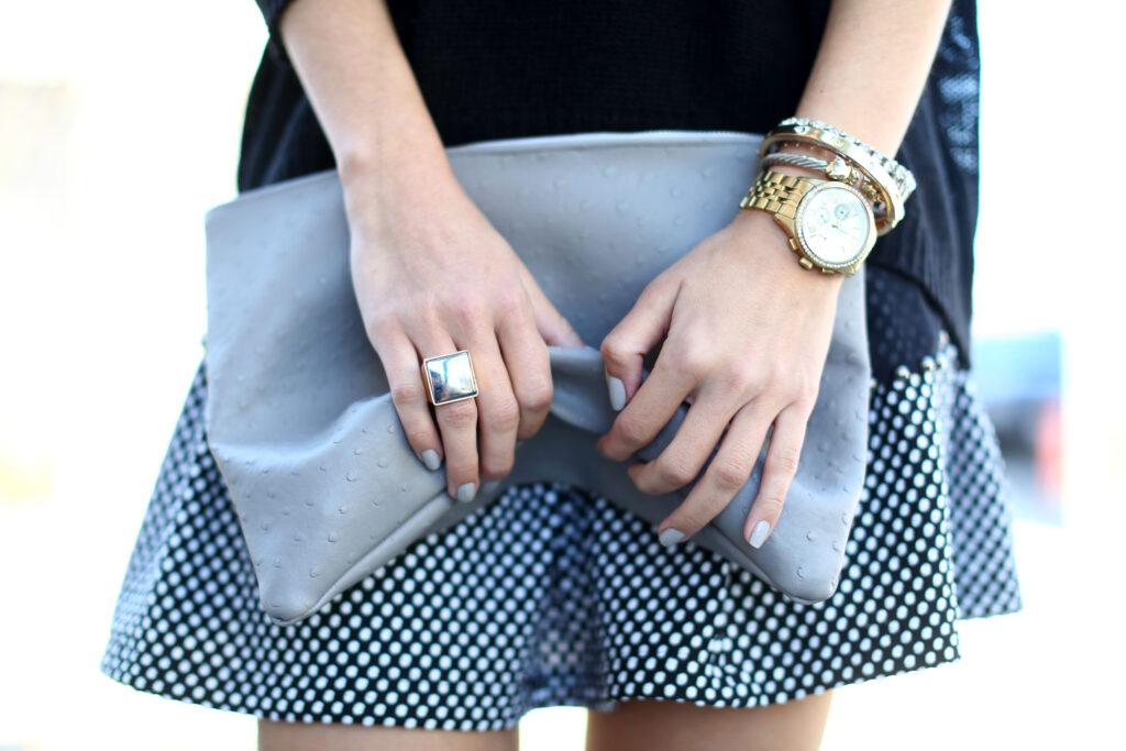 modelka z szarą kopertówką, zegarkiem i bransoletkami
