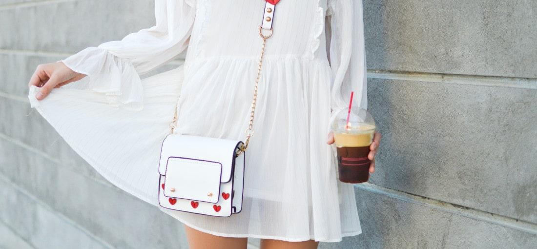 kobieta w białej sukience i kopertówce